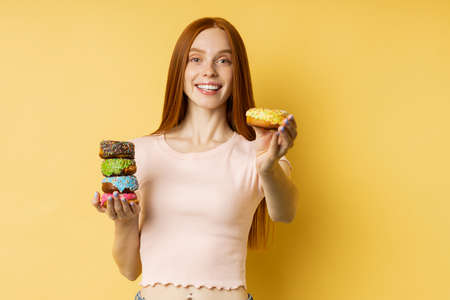 Young woman wearing casual clothes holding delicious sweet glazed doughnuts, being on diet and cant eat sweets, feeling temptation, standing over yellow background with copy space.