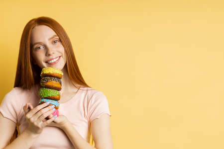 Horizontal closeup shot of pleased redhead woman holding colorful decorated donuts, broadly smiling looking at camera, enjoying sweets, isolated yellow background with copy space for your advertising.