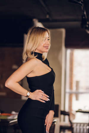 A blonde woman in a black dress stands sideways in the room and smiles