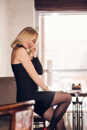 Blonde woman flirting looks at the camera in a restaurant, cafe. A girl wearing a short black dress is sitting on the sofa and smiling