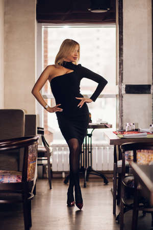 A full length blonde woman stands in a short black dress and red shoes in a restaurant and looks away smiling Banque d'images