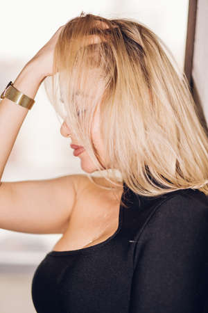 Blonde woman sideways profile closeup. A girl with short hair covers her eyes and hands on her head