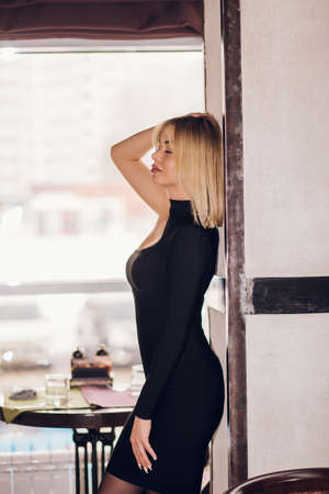 A woman is standing sideways by the window. A blonde girl with short hair in a black dress with her eyes closed smiles and leans against the wall in a restaurant