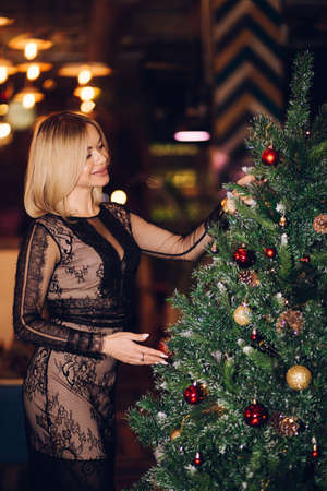 Blonde woman decorating the Christmas tree. The girl puts on a Lacy elegant black dress, smiles. Happiness, emotions, Christmas, new year, holiday
