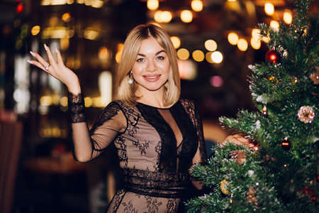 Christmas a woman smiles near the Christmas tree and looks at the camera. Blonde girl wearing black dress indoors with bokeh lights background