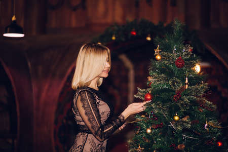 A woman decorates a Christmas tree at home. Holiday, corporate, new year, Christmas concepts