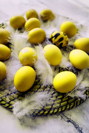 Abstract yellow eggs on white fluff closeup. Easter spring concept