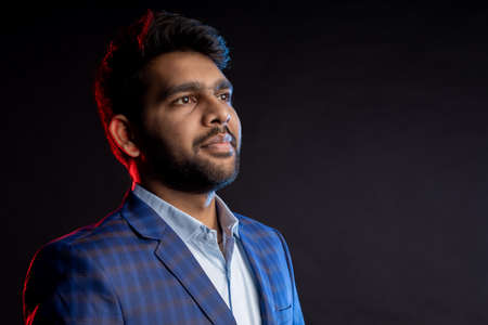 Closeup portrait of young handsome confident serious bearded Indian businessman with stylish haircut, wearing shirt, checked suit, standing against black background. Stock fotó