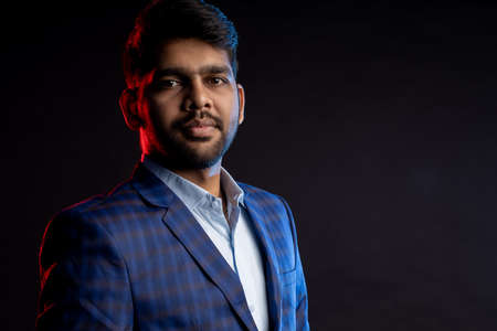 Closeup portrait of young handsome confident serious bearded Indian businessman with stylish haircut, wearing shirt, checked suit, looking at camera, standing against black background.