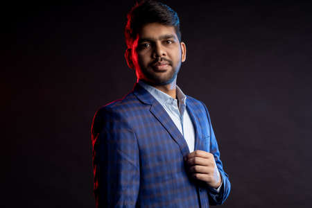 handsome confident bearded Indian man, businessman wearing shirt, checked suit, black hat, looking aside, standing isolated on dark background.
