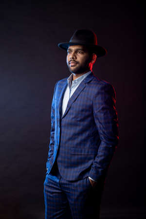 Vertical shot of confident young Indian businessman wearing checkered suit, shirt, black hat, standing with hands in pockets, posing against dark background. Successful businessman.