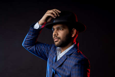 Closeup portrait of young handsome confident bearded Indian man, businessman wearing shirt, checked suit, black hat, looking aside, standing isolated on dark background. Stock fotó