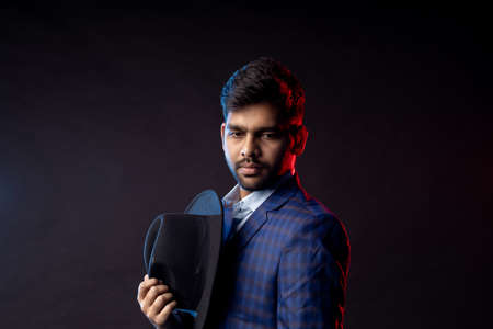Closeup portrait of young handsome confident serious bearded Indian man, businessman with stylish hairstyle, wearing shirt, checkered suit standing against dark background, holding in hand black hat. Stock fotó