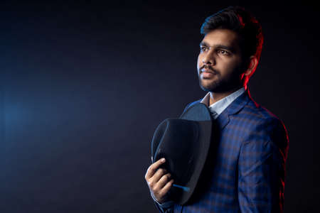 Indian man, businessman wearing shirt, checked suit, black hat, looking aside, standing isolated on dark background. Stock fotó
