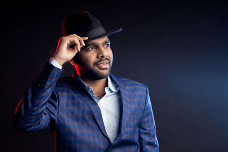 Studio portrait of young handsome confident unshaven Indian man, businessman wearing shirt, checked suit, looking at camera, touching hat, smiling, standing isolated on dark background.