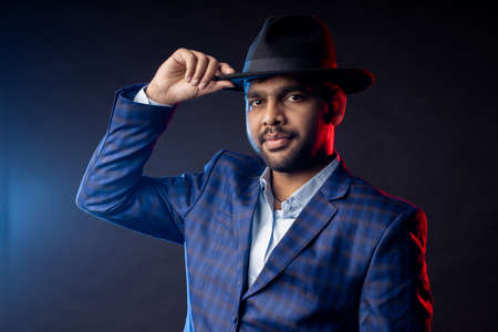 Indian man, businessman wearing shirt, checked suit, looking at camera, touching hat, smiling, standing on dark background.