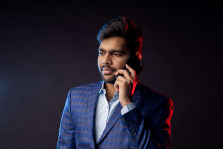 Horizontal shot of serious stylish young indian man in suit, holding smartphone, looking to side, talking on cell phone, standing against black background. Successful businessman. Copy space.