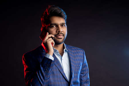 indian man holding mobile phone, looking at screen, standing against black background. Successful businessman. Business, technology. Stock fotó