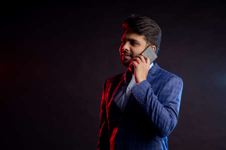 indian man in suit, holding smartphone, looking to side, talking on cell phone, standing against black background. Successful businessman. Copy space.