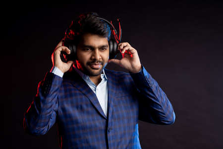 Portrait of happy indian male customer service representative, operator of hotline, call center worker, speaking with headset, isolated on black background. Businessman listening music in headphones.