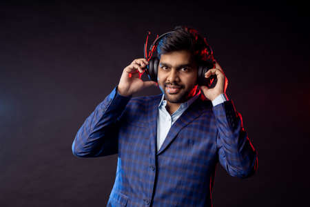 Businessman in formal wear listening music in headphones. Studio closeup shot of young indian unshaven man with headset, wearing checked suit, isolated over black background. Stock fotó
