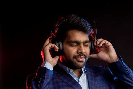 indian unshaven man with headset, wearing checked suit, isolated over black background.