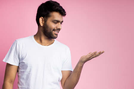 Handsome young indian man with stubble, wearing white t shirt, holding on palm copy space, demonstrating product, smiling looking at camera, isolated on pink background. Advertisement concept. Stock fotó