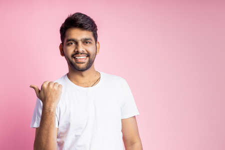 Waist-up shot of cheerful carefree indian man with stubble, wearing white t shirt, pointing left with thumb, laughing, looking at camera, standing over pink background. Advertising concept. Stock fotó