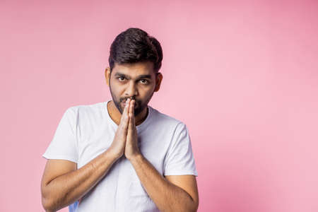 Young religious indian unshaven man wearing white t shirt, keeping palms together, looking down, praying, hoping for best, isolated over in pink background. Belief concept.