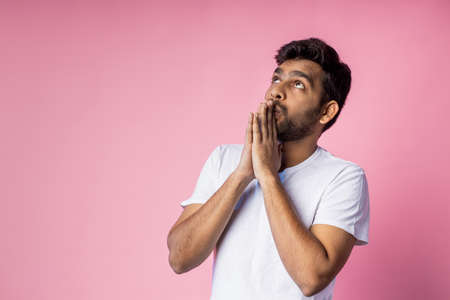 Closeup of young indian male in white t shirt, praying with palms clasped together, asking the God for good luck, success, health, on pink background with copy space. Human emotion, belief concept.