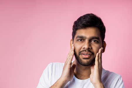 Stunned handsome unshaven indian male, being shocked by low prices on sale, keeping hands on cheeks, opening mouth in surprise, isolated over pink background. Emotions, reactions concept. Copy space. Stock fotó