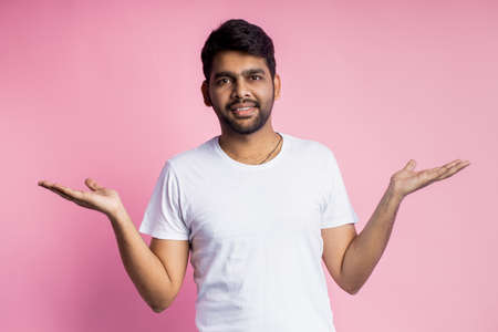Waist up shot of bewildered indian man spreading hands, wearing white t shirt, looking at camera puzzled, doesn't understand what happened, on pink background. Emotions, expressions, gesture concept.