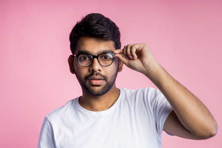 Serious indian young man with bad eyesight, looking thoroughly through glasses, trying to read something, touching frame of eyewear, wearing casual outfit, isolated on pink background with copy space.