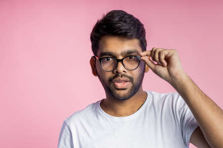 indian young man with bad eyesight, looking thoroughly through glasses, trying to read something, touching frame of eyewear, wearing casual outfit, isolated on pink background with copy space.
