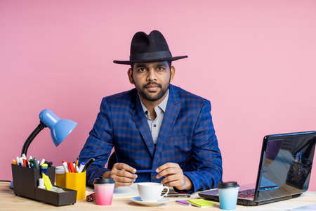 Indian businessman wearing suit, black hat, looking at screen of mobile phone, waiting for important call, reading news, sending email, sitting at working desk in office, over pink background.