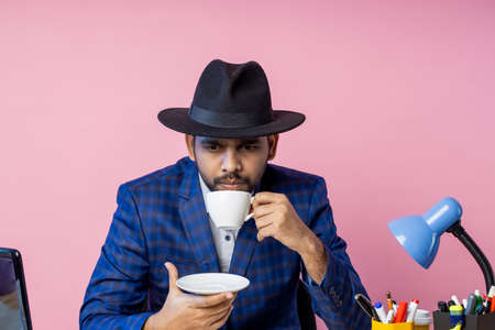office worker, businessman in formal checkered suit, black hat, sitting at workplace, thinking about something, looking aside, enjoying aromatic coffee. Business, lifestyle, people concept.