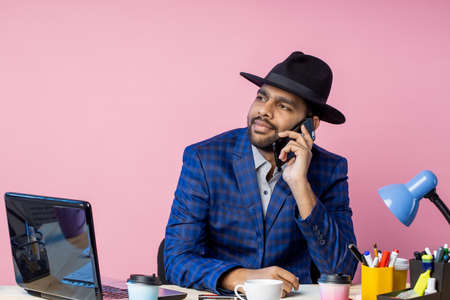 Joyful stylish indian entrepreneur wearing formal wear, black hat, talking on mobile phone, smiling broadly, looking to side, sitting at desk in office against pink wall. Job, business concept.