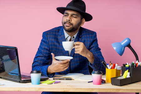 young unshaven indian businessman in formal blue checkered suit, black hat, sitting at workplace, thinking about something, looking aside, enjoying aromatic coffee or tea. Stock fotó