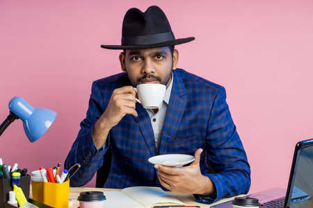 businessman in formal checkered suit, black hat, sitting at workplace, thinking about something, looking aside, enjoying aromatic coffee. Business, lifestyle, people concept.
