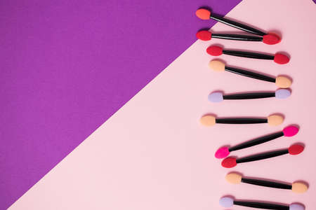 Lots of colorful eyeshadow applicators on a bright purple pink two tone background with copy space. Cosmetics, beauty, youth, care, professional makeup artist concept Stock fotó