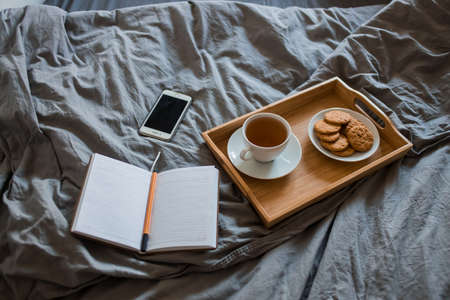 Top view a Cup of tea with cookies on a tray and an open notebook, a pen on a gray bed with a copy space ..