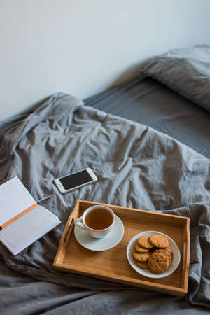 Breakfast of tea and biscuits with a Notepad and pen in a gray bed in the morning Stock fotó