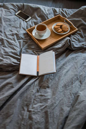 Breakfast of tea and biscuits with a magazine in a gray bed in the morning