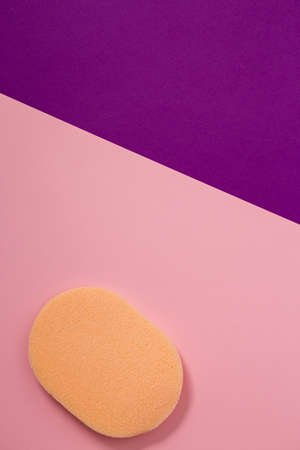 orange cosmetic sponge for makeup on pink background
