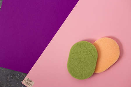 Closeup top view of two beautiful large green and yellow makeup sponges on pink background with copy space