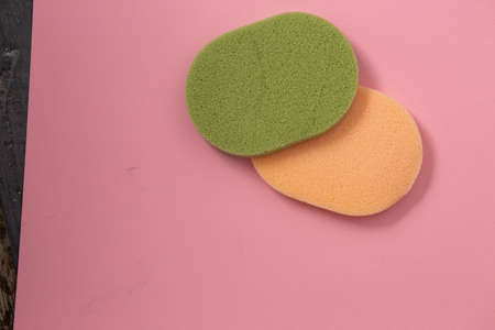two beautiful large green and yellow makeup sponges on pink background with copy space