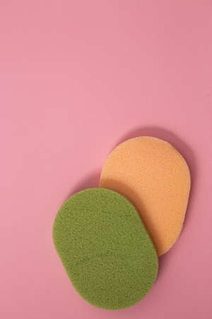 Closeup top view of two beautiful large green and yellow makeup sponges