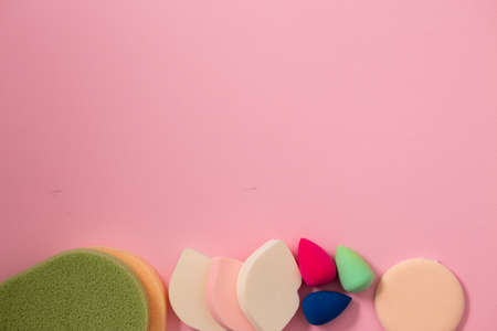 Closeup of beautiful green, yellow, blue, pink and white makeup sponges on paper background with copy space