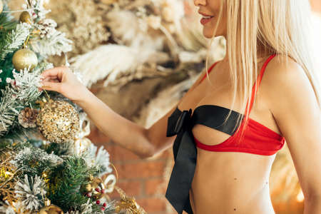 Blonde woman in lingerie decorates Christmas tree and smiles on Christmas background