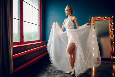 A slender girl in a beige dress is standing in front of the window holding on to the hem of the dress